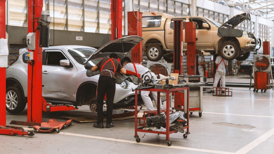 vehicle repair shop, employees working on a car, best garage liability insurance coverage