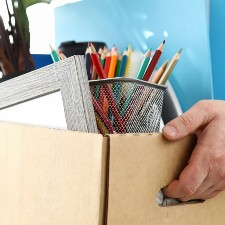 a person is holding a moving box with pens, a picture frame, and other personal things somebody could have on their desk, EPLI insurance, management liability insurance