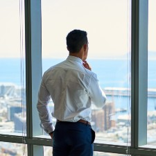 business man with white shirt and black pants, looking out of the window that oversees the coast, management liability insurance