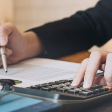 a person is using a calculator to check numbers, fiduciary liability insurance, management liability insurance