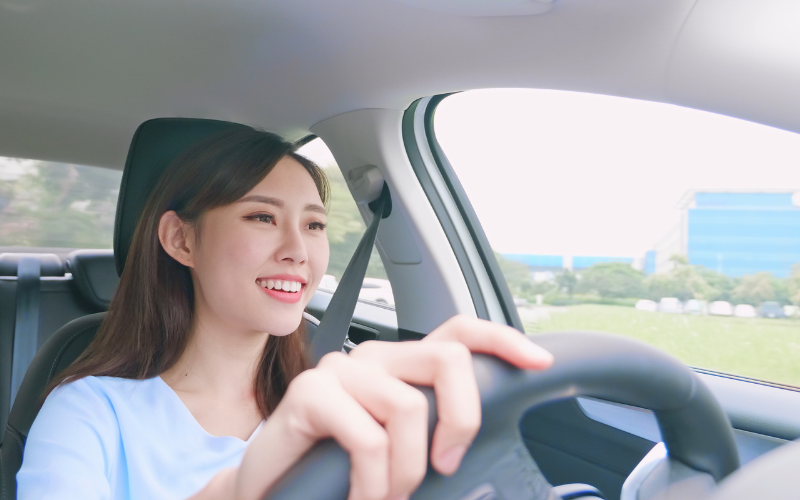 woman driving a car, smiling, How to Lower Car Insurance Premium Costs