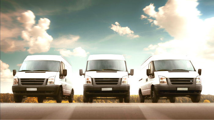 Three white delivery trucks parked in a row against the sky with clouds, JAISIN Insurance Solutions