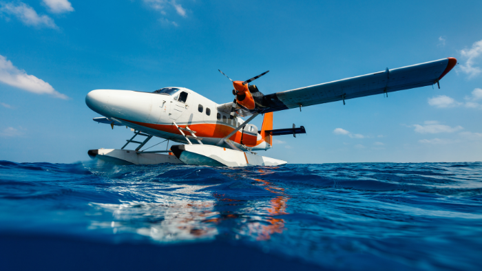a white seaplane with red and orange stripes floats on the ocean