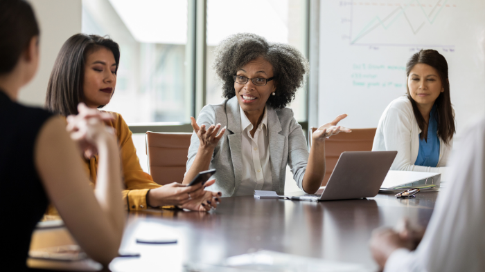 five corporate executive women sit at a meeting table, the head executive gesturing with a laptop, JAISIN Insurance Solutions