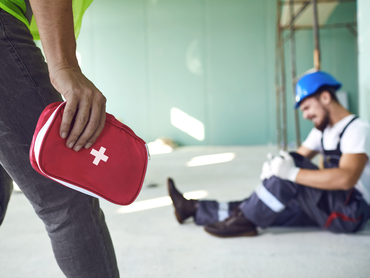 a construction worker holding his injured knee sits on a work site while his coworker approaches with a first aid kit, JAISIN Insurance Solutions