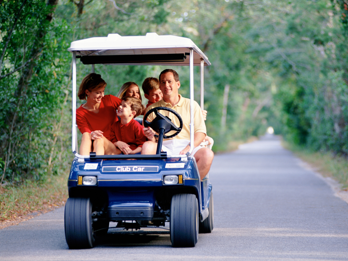 a family of four driving a blue golf cart down a paved path in nature