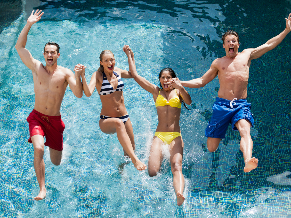 two young men and two young women jump into a pool