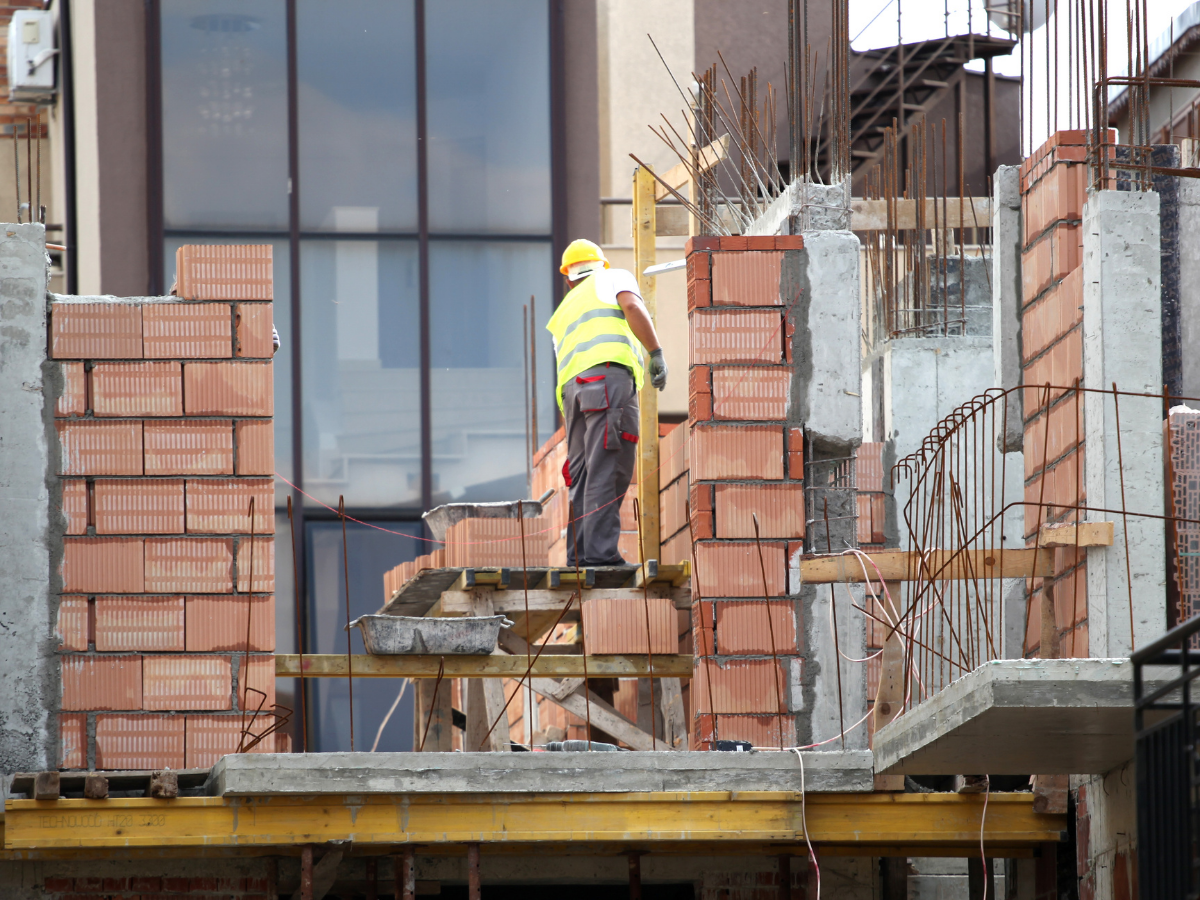 a construction worker stands on home construction site and lays large bricks
