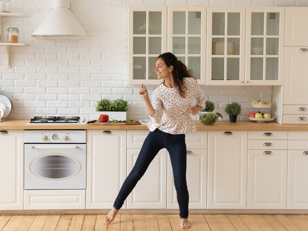 a young brunette woman in a white blouse and black pants dances in her white apartment kitchen