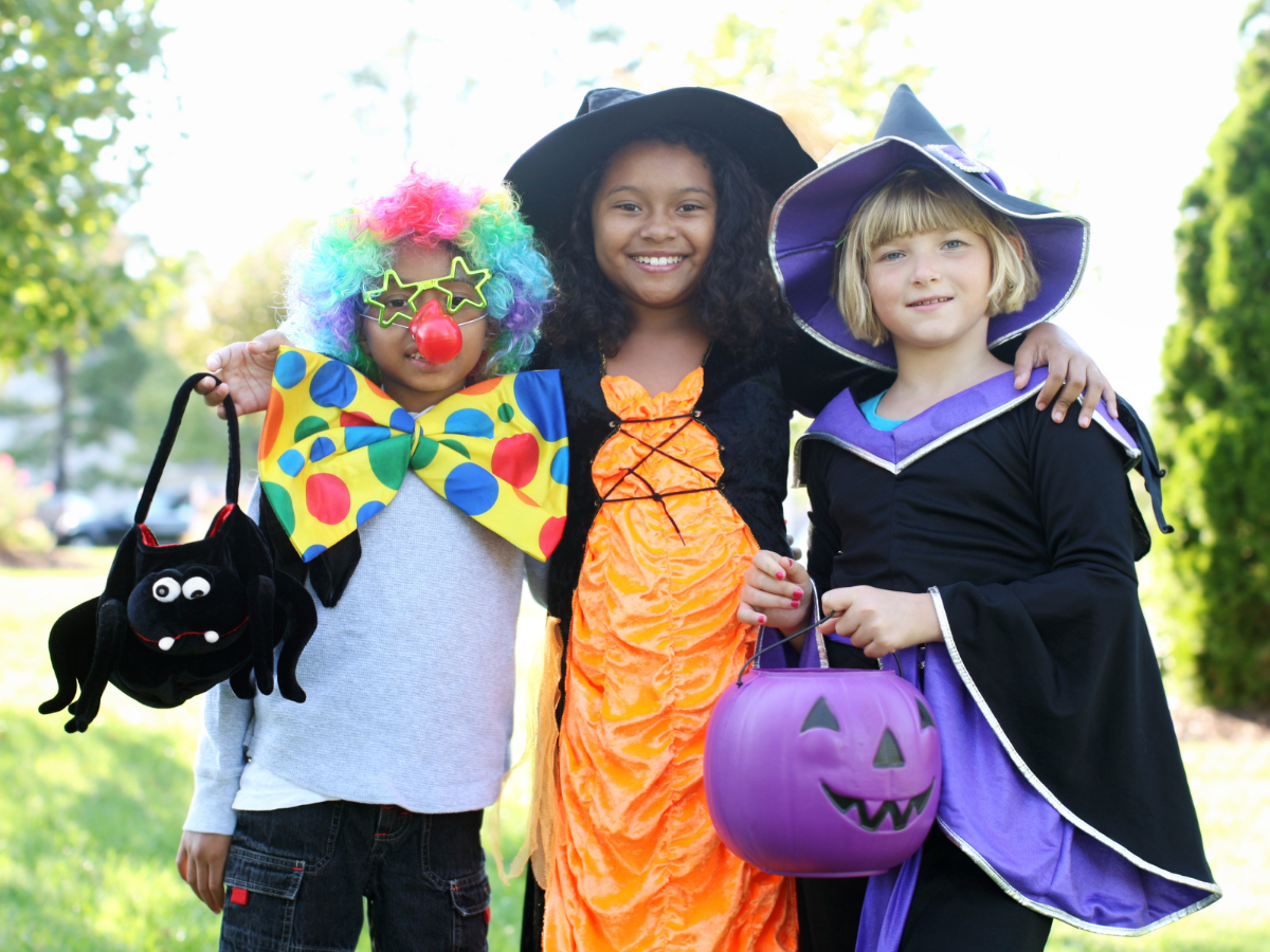 three elementary school kids dress up as a clown, an orange witch, and a purple witch for Halloween