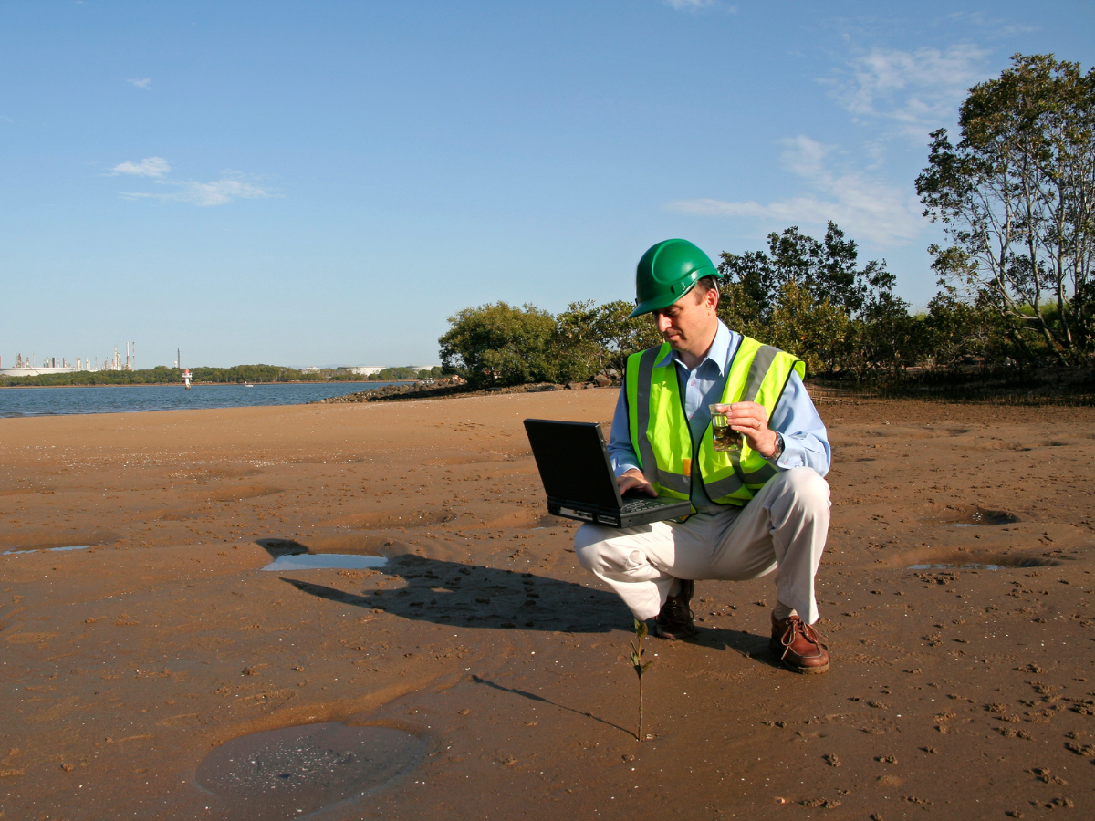 an environmental inspector in a neon yellow vest, hard hat, and khakis holds a laptop while kneeling on a beach