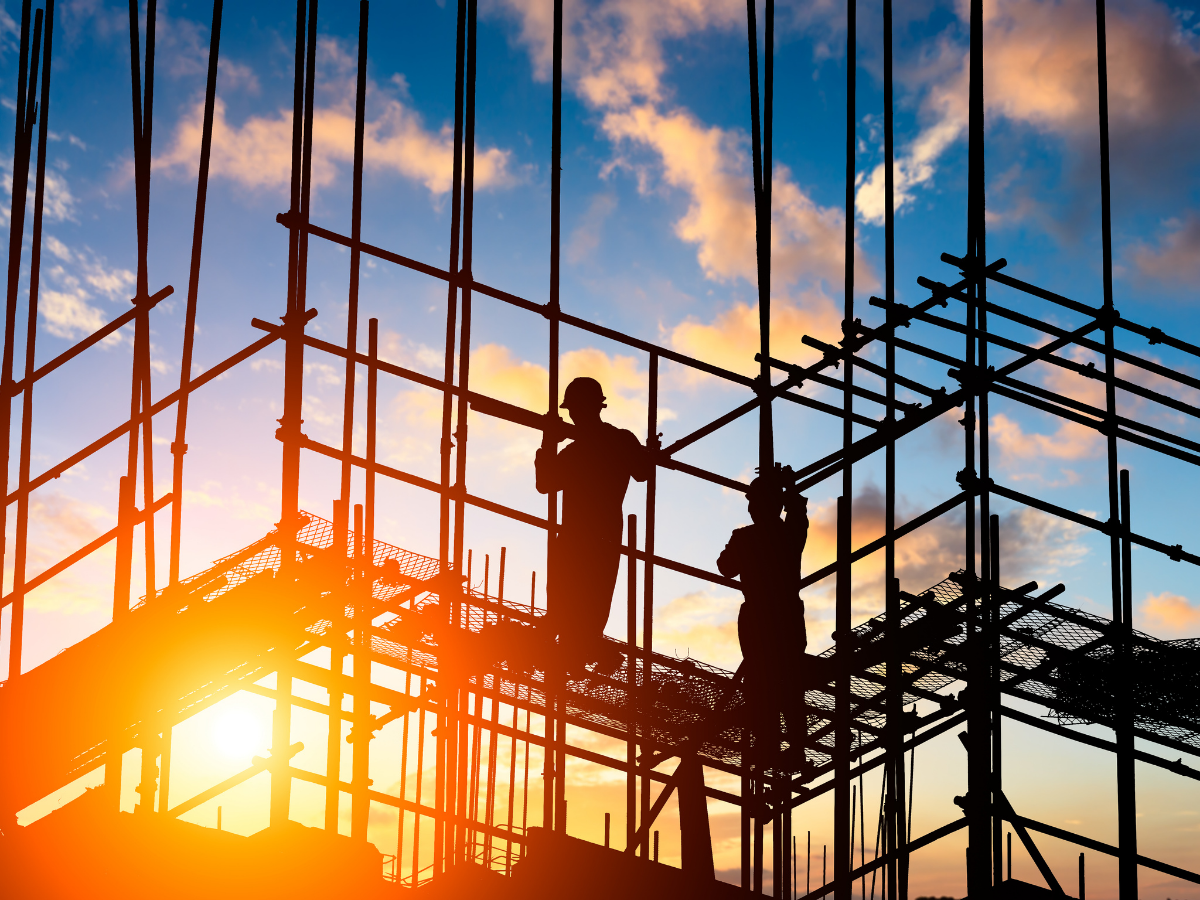 two construction workers standing on scaffolding at sunset